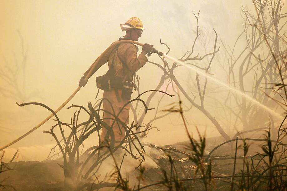 A firefighter dousesflare-ups while battling a wildfire along the Pacific Coast Highway near Naval Base Ventura 