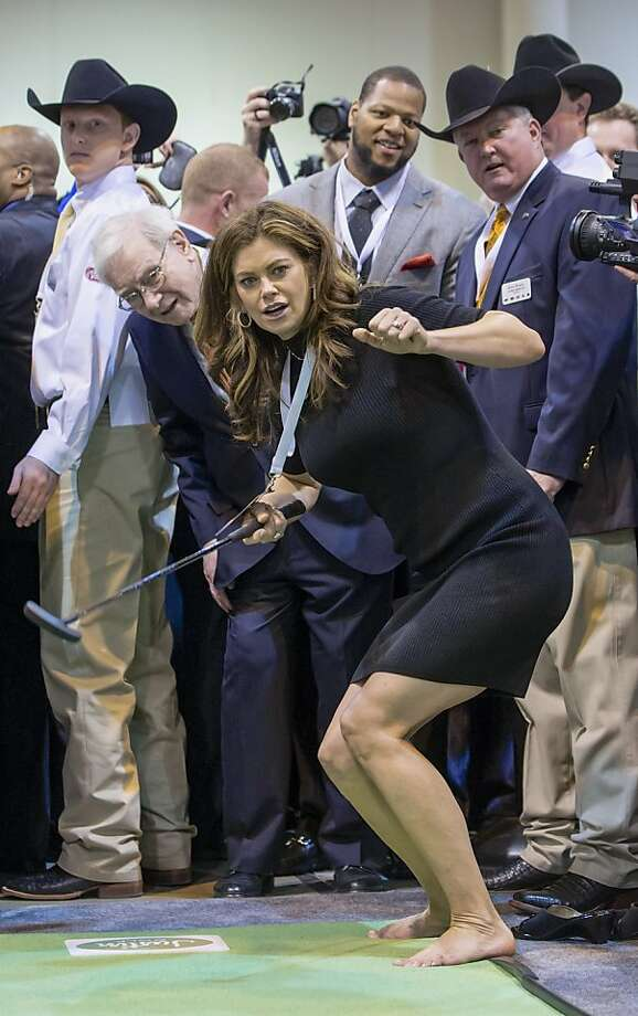 Former supermodel and now businesswoman Kathy Ireland and Berkshire Hathaway Chairman and CEO Warren Buffett follow Ireland's golf putting prior to the Berkshire Hathaway shareholders meeting in Omaha, Neb., Saturday, May 4, 2013. At center top is Detroit Lions defensive tackle Ndamukong Suh. Tens of thousands attend Berkshire Hathaway shareholders meetings to hear Buffett and Charlie Munger answer questions. No other annual meeting can rival Berkshire's, which is known for its size, the straight talk Buffett and Munger offer and the sales records shareholders set while buying Berkshire products. (AP Photo/Nati Harnik) Photo: Nati Harnik, Associated Press