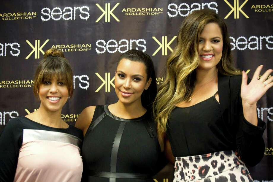 Kourtney, left, Kim and Khloe Kardashian pose for photos as they arrive to an appearance at the Sears Willowbrook Mall Saturday, May 4, 2013, in Houston. The Kardashian sisters appeared before a huge crowd of fans to celebrate the Spring 2013 Kardashian Kollection. Photo: Brett Coomer, Houston Chronicle / © 2013 Houston Chronicle