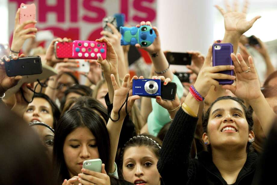 Fans of the Kardashian sisters take photos as they arrive to an appearance at the Sears Willowbrook Mall Saturday, May 4, 2013, in Houston. The Kardashian sisters appeared before a huge crowd of fans to celebrate the Spring 2013 Kardashian Kollection. Photo: Brett Coomer, Houston Chronicle / © 2013 Houston Chronicle