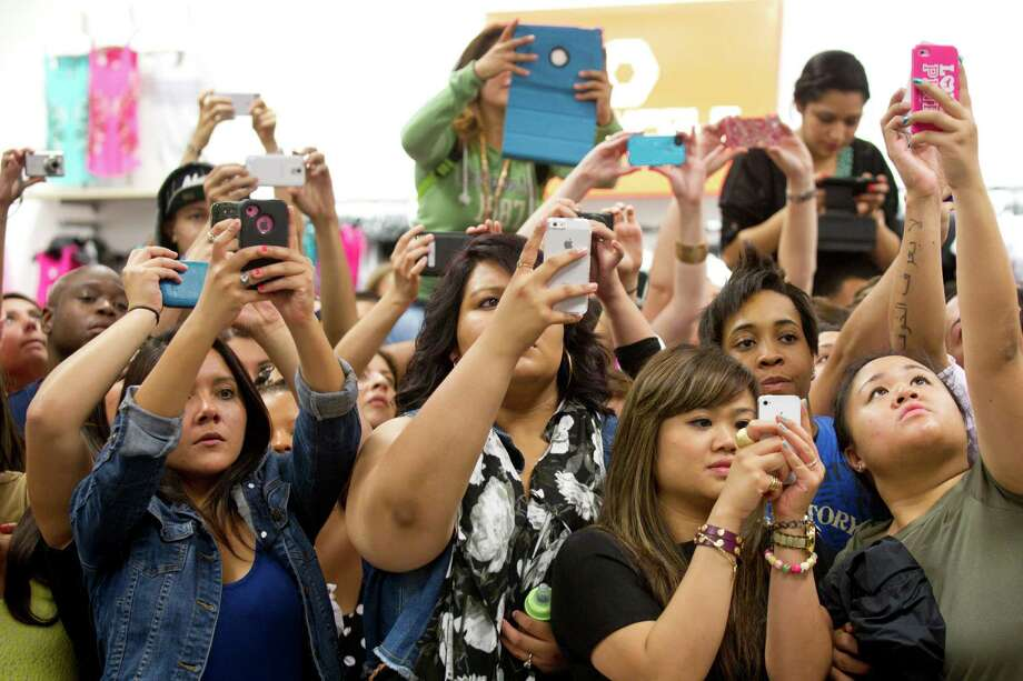 Fans of Kim, Khloe and Kourtney Kardashian take photos as the sisters arrive to an appearance at the Sears Willowbrook Mall Saturday, May 4, 2013, in Houston. The Kardashian sisters appeared before a huge crowd of fans to celebrate the Spring 2013 Kardashian Kollection. Photo: Brett Coomer, Houston Chronicle / © 2013 Houston Chronicle
