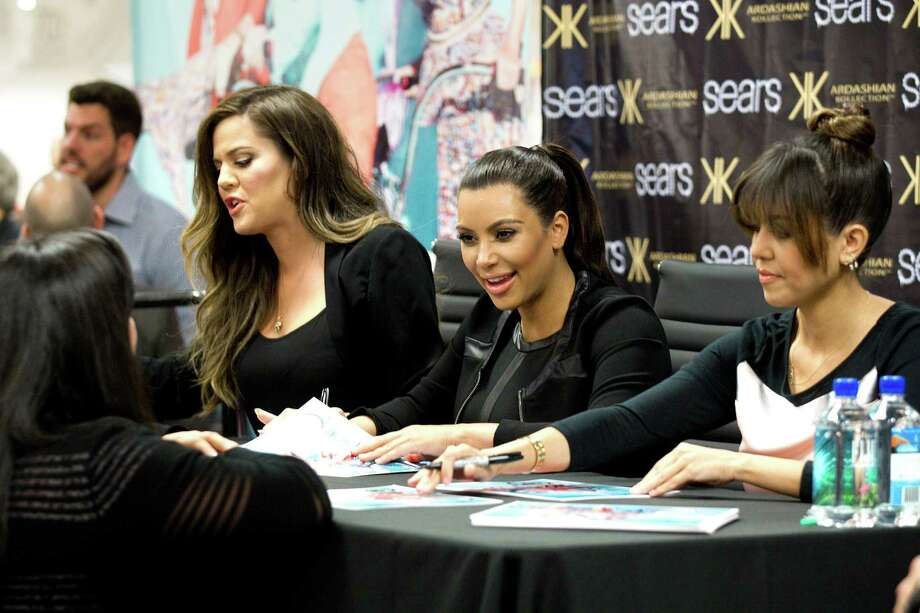 Khloe, left, Kim and Kourtney Kardashian sign autographs during an appearance at the Sears Willowbrook Mall Saturday, May 4, 2013, in Houston. The Kardashian sisters appeared before a huge crowd of fans to celebrate the Spring 2013 Kardashian Kollection. Photo: Brett Coomer, Houston Chronicle / © 2013 Houston Chronicle