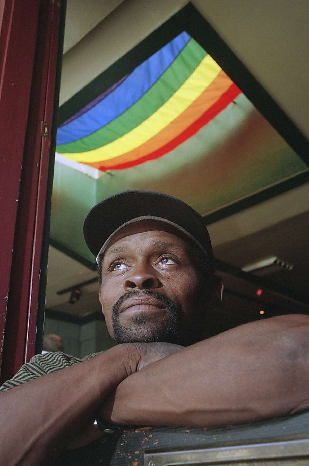 Former Major League Baseball player Glenn Burke sits in a Castro District restaurant in San Francisco in 1993. Burke is dying of AIDS. The Rainbow flag signifying Gay Pride hangs behind him. (AP Photo/Mark Hundley)