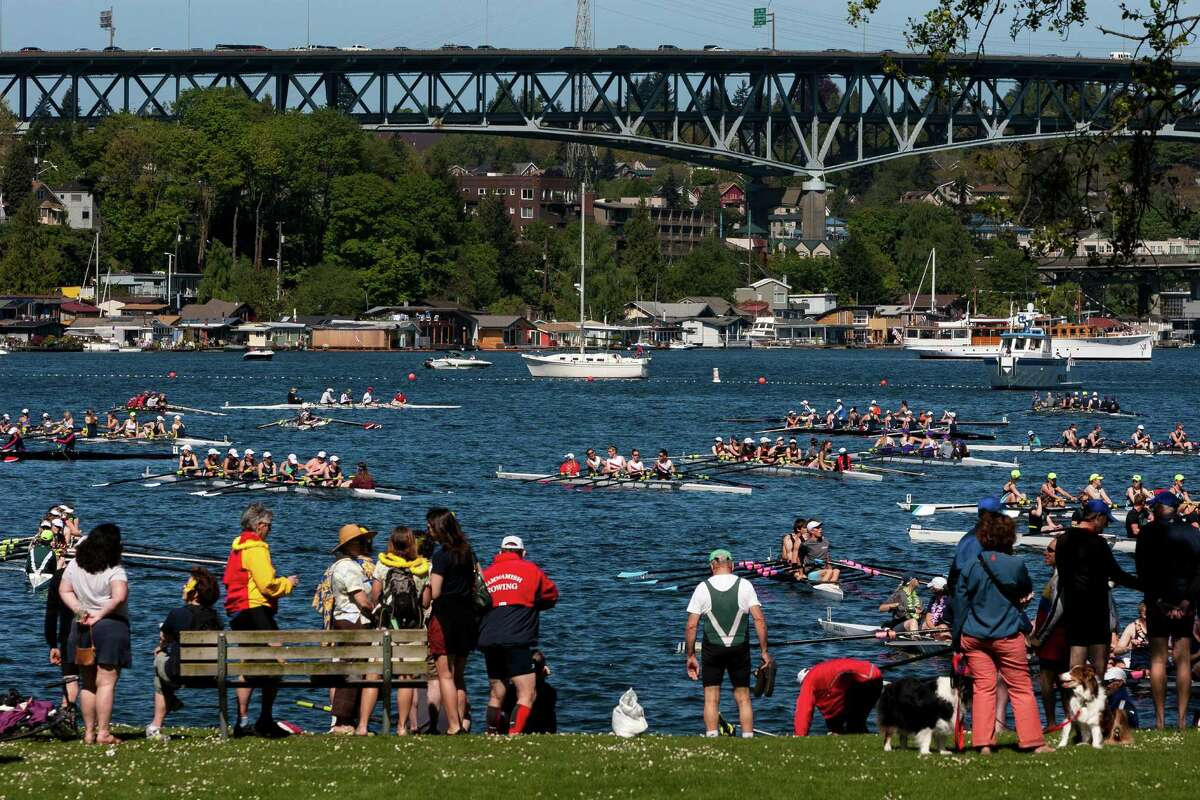 Crowds clustered along the water's edge of the Montlake Cut to enjoy a sunny opening day of boating season, the Windermere Cup and the boat parade Saturday, May 4, 2013, in Seattle. The University of Washington's male and female rowing teams took home the gold in the Windermere Cup.