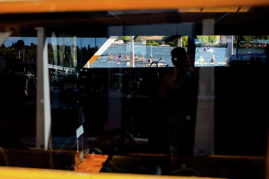 Rowers are pictured through a yacht window amidst reflections of the surrounding marina on the opening day of boating season, the Windermere Cup and the boat parade Saturday, May 4, 2013, in Seattle. The University of Washington's male and female rowing teams took home the gold in the Windermere Cup. Photo: JORDAN STEAD, SEATTLEPI.COM / SEATTLEPI.COM