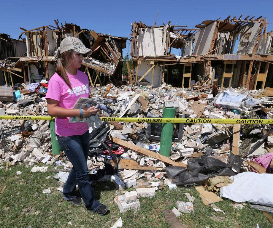Texas A&M University freshman Heather Warfield collects baseball cards from a nearby apartment complex, Saturday, May 4, 2013, in West Texas. Over 124 students donated their time to help cleanup parts of West devastated by the fertilizer plant explosion. The plant exploded during a fire April 17, killing at least 14 people and injuring about 200. (AP Photo/Waco Tribune Herald, Rod Aydelotte) Photo: Rod Aydelotte