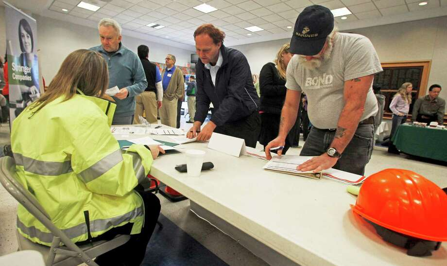 In this Thursday, April 3, 2013 photo, people fill out applications at the Green Mountain Flagging table at the annual Central Vermont Job Fair in Montpelier, Vt. The American economy and job market are moving in the right direction, just not very quickly. The news Friday, May 3, 2013, that U.S. employers added a solid 165,000 jobs in April and unemployment fell to a four-year low 7.5 percent came as a relief. (AP Photo/Toby Talbot) Photo: Toby Talbot, STF / AP