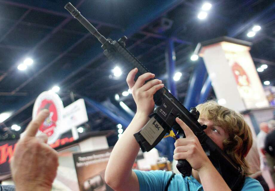 James Beaver, 13, of Denison, holds an HK 416 D at the NRA Whittington Center Outdoor Adventure exhibit booth at the National Rifle Association's 142 Annual Meetings and Exhibits in the George R. Brown Convention Center Friday, May 3, 2013, in Houston. Photo: Johnny Hanson, Houston Chronicle / © 2013  Houston Chronicle