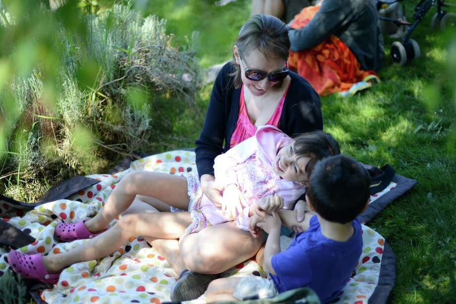 Melissa Liu tickles her daughter, Izzie, 6, and her son Simon, 3, as they relax near the water at the 27th Windermere Cup at the Montlake Cut on Saturday, May 4, 2013. The University of Washington men's and women's teams swept all four premier events this year, giving the varsity teams their seventh straight Windermere Cup win. (Photo by Lindsey Wasson) Photo: LINDSEY WASSON, LINDSEY WASSON/SEATTLEPI.COM / SEATTLEPI.COM