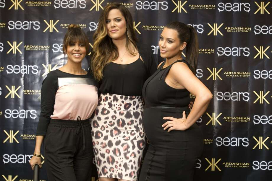 Kourtney, left, Khloe and Kim Kardashian pose for photos as they arrive to an appearance at the Sears Willowbrook Mall Saturday.