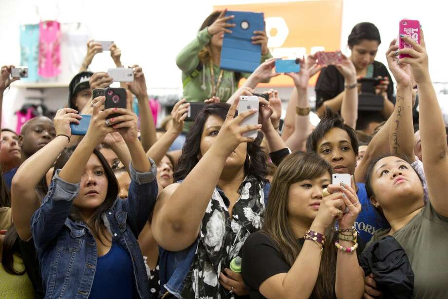 Fans of Kim, Khloe and Kourtney Kardashian take photos as the sisters arrive to an appearance at the Sears Willowbrook Mall Saturday.
