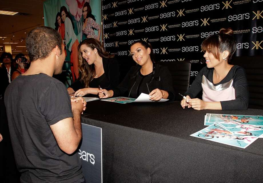 HOUSTON, TX - MAY 04:  (L-R)  Khloe Kardashian Odom, Kim Kardashian and The Kardashians sign autographs for fans during a Sears In-Store Appearance For Kardashian Kollection  at Willowbrook Mall