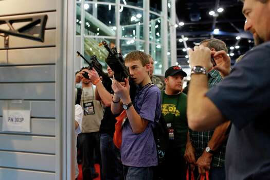 14-year-old Caleb Lofton, middle poses with a rifle while his father, James, right, takes a photo, during day 2 of the 142nd NRA annual meetings and exhibits, Saturday, May 4, 2013 at the George R Brown convention center in Houston, Texas. (TODD SPOTH FOR THE CHRONICLE) Photo: © TODD SPOTH, 2013 / © TODD SPOTH, 2013