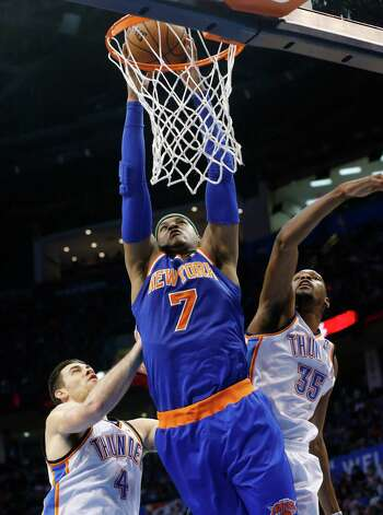 New York Knicks forward Carmelo Anthony (7) dunks between Oklahoma City Thunder forward Nick Collison (4) and forward Kevin Durant (35) in the second quarter of an NBA basketball game in Oklahoma City, Sunday, April 7, 2013. (AP Photo/Sue Ogrocki) Photo: Associated Press / AP