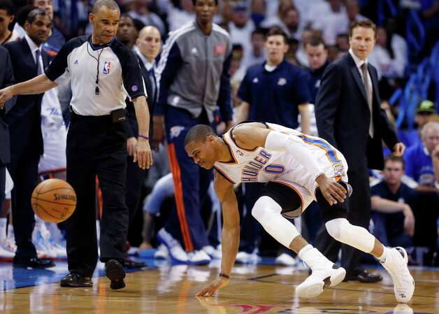In this photo taken Wednesday, April 24, 2013, Oklahoma City Thunder guard Russell Westbrook stumbles after injuring his right knee in the second quarter of Game 2 of a first-round NBA basketball playoff series against the Houston Rockets in Oklahoma City. Westbrook, who remained in the game, will have surgery to repair a torn meniscus in his right knee and be out indefinitely, dealing a harsh blow to the City Thunder�s championship chances. (AP Photo/Sue Ogrocki) Photo: Associated Press / AP
