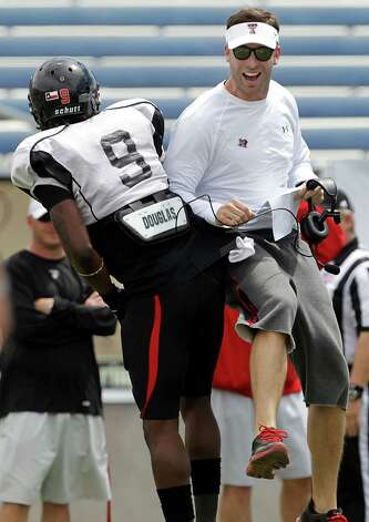 In this photo taken Saturday, April 6, 2013, Texas Tech coach Kilff Kingsbury celebrates a touchdown with Shawn Corker (9) during NCAA college football practice in Midland, Texas. (AP Photo/Lubbock Avalanche-Journal, Stephen Spillman) LOCAL TV OUT Photo: Associated Press / Lubbock Avalanche-Journal
