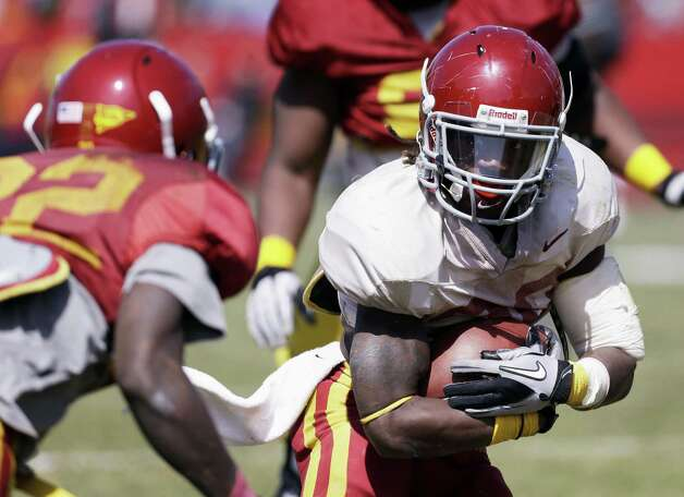Running back DeVondrick Nealy (right), trying to avoid defensive back T.J. Mutcherson in the spring game, could be a breakaway threat for Iowa State. Photo: Charlie Neibergall / Associated Press