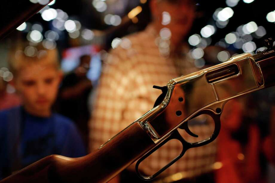Expo attendees inspect a rifle, during day 2 of the 142nd NRA annual meetings and exhibits, Saturday, May 4, 2013 at the George R Brown convention center in Houston, Texas. (TODD SPOTH FOR THE CHRONICLE) Photo: © TODD SPOTH, 2013 / © TODD SPOTH, 2013