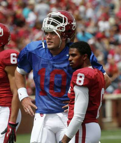 Oklahoma quarterback Blake Bell (10) talks with wide receiver Jalen Saunders (8) before the start of the Oklahoma spring intra-squad NCAA college football game in Norman, Okla., Saturday, April 13, 2013. (AP Photo/Sue Ogrocki) Photo: Associated Press / AP