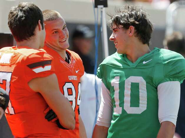 Oklahoma State quarterback Clint Chelf (10) talks with teammates wide receiver Charlie Moore (17) and wide receiver Austin Hays (84) during the Oklahoma State spring NCAA college football game in Stillwater, Okla., Saturday, April 20, 2013. (AP Photo/Sue Ogrocki) Photo: Associated Press / AP