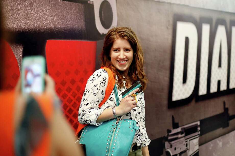 Shelby Zeltmann of San Francisco poses with a pistol, during day 2 of the 142nd NRA annual meetings and exhibits, Saturday, May 4, 2013 at the George R Brown convention center in Houston, Texas. (TODD SPOTH FOR THE CHRONICLE) Photo: © TODD SPOTH, 2013 / © TODD SPOTH, 2013