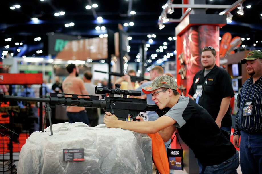 Grant Siebrecht of Needville inspects a rifle, during day 2 of the 142nd NRA annual meetings and exhibits, Saturday, May 4, 2013 at the George R Brown convention center in Houston, Texas. (TODD SPOTH FOR THE CHRONICLE) Photo: © TODD SPOTH, 2013 / © TODD SPOTH, 2013