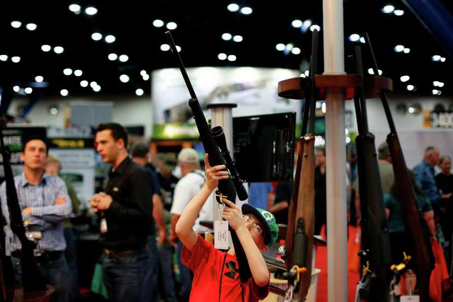 11-year-old Ryan Weaver inspects a rifle, during day 2 of the 142nd NRA annual meetings and exhibits, Saturday, May 4, 2013 at the George R Brown convention center in Houston, Texas. (TODD SPOTH FOR THE CHRONICLE) Photo: © TODD SPOTH, 2013 / © TODD SPOTH, 2013