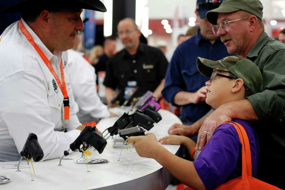 A father and son browse pistols, during day 2 of the 142nd NRA annual meetings and exhibits, Saturday, May 4, 2013 at the George R Brown convention center in Houston, Texas. (TODD SPOTH FOR THE CHRONICLE) Photo: © TODD SPOTH, 2013 / © TODD SPOTH, 2013