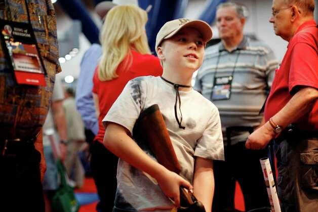 10-year-old Bryce Danforth of St. Augustine, Florida inspects a rifle while his grandfather watches closely, during day 2 of the 142nd NRA annual meetings and exhibits, Saturday, May 4, 2013 at the George R Brown convention center in Houston, Texas. (TODD SPOTH FOR THE CHRONICLE) Photo: © TODD SPOTH, 2013 / © TODD SPOTH, 2013