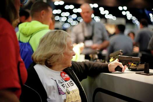 An expo attendee inspects a Glock pistol, during day 2 of the 142nd NRA annual meetings and exhibits, Saturday, May 4, 2013 at the George R Brown convention center in Houston, Texas. (TODD SPOTH FOR THE CHRONICLE) Photo: © TODD SPOTH, 2013 / © TODD SPOTH, 2013