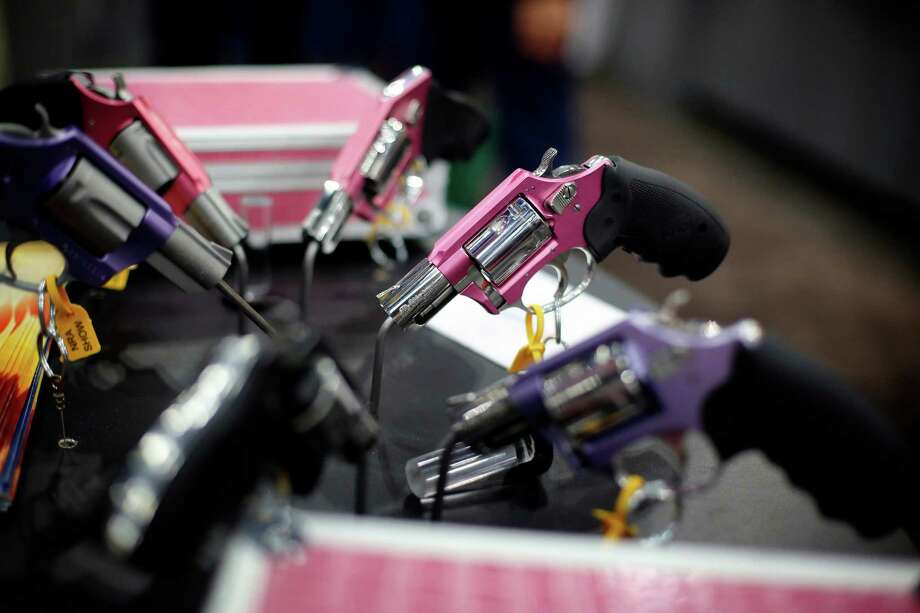 A display of pistols painted pink and purple is seen, during day 2 of the 142nd NRA annual meetings and exhibits, Saturday, May 4, 2013 at the George R Brown convention center in Houston, Texas. (TODD SPOTH FOR THE CHRONICLE) Photo: © TODD SPOTH, 2013 / © TODD SPOTH, 2013
