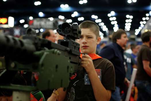 13-year-old Jacob La looks down the sight of a mounted machine gun, during day 2 of the 142nd NRA annual meetings and exhibits, Saturday, May 4, 2013 at the George R Brown convention center in Houston, Texas. (TODD SPOTH FOR THE CHRONICLE) Photo: © TODD SPOTH, 2013 / © TODD SPOTH, 2013