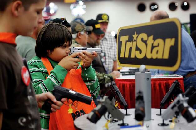 Brothers, 10-year-old Kayden La, middle, and 13-year-old Jacob La, left, inspect pistols at a booth, during day 2 of the 142nd NRA annual meetings and exhibits, Saturday, May 4, 2013 at the George R Brown convention center in Houston, Texas. (TODD SPOTH FOR THE CHRONICLE) Photo: © TODD SPOTH, 2013 / © TODD SPOTH, 2013