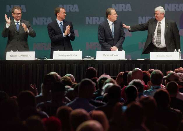 NRA executive vice president Wayne LaPierre is applauded next to NRA President David Keene, right, and Chris Cox, executive director NRA-ILA and Wilson Phillips Jr., treasurer, during the NRA Annual Meeting of Members at the National Rifle Association's 142 Annual Meetings and Exhibits in the George R. Brown Convention Center Saturday, May 4, 2013, in Houston. Photo: Johnny Hanson, Houston Chronicle / © 2013  Houston Chronicle