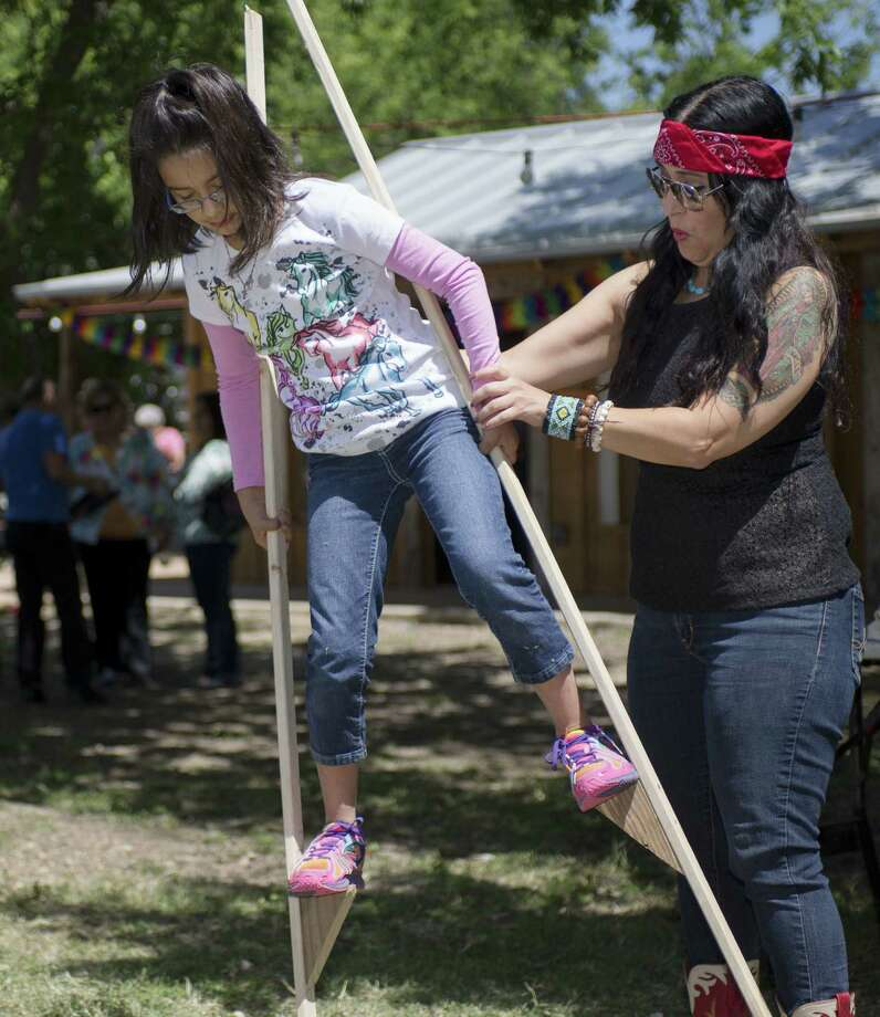 Marisela Barrera (right) helps 8-year-old daughter, Valentina Barrera-Ibarra, walk on stilts during Paseo Por El Westside. Photo: Darren Abate / For The San Antonio Express-News