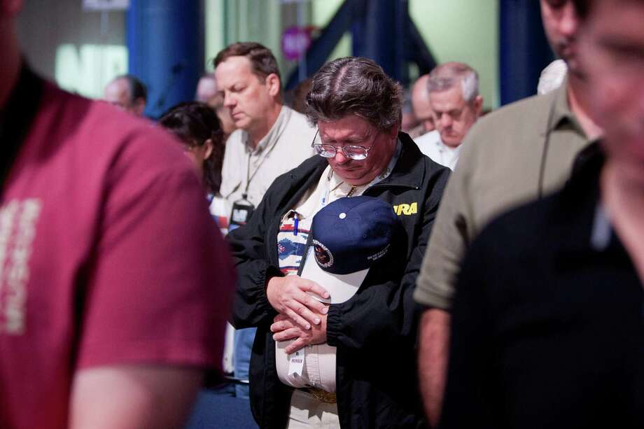 An NRA member prays during the NRA Annual Meeting of Members at the National Rifle Association's 142 Annual Meetings and Exhibits in the George R. Brown Convention Center Saturday, May 4, 2013, in Houston. Photo: Johnny Hanson, Houston Chronicle / © 2013  Houston Chronicle
