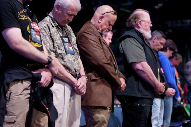 NRA members pray during the NRA Annual Meeting of Members at the National Rifle Association's 142 Annual Meetings and Exhibits in the George R. Brown Convention Center Saturday, May 4, 2013, in Houston. Photo: Johnny Hanson, Houston Chronicle / © 2013  Houston Chronicle
