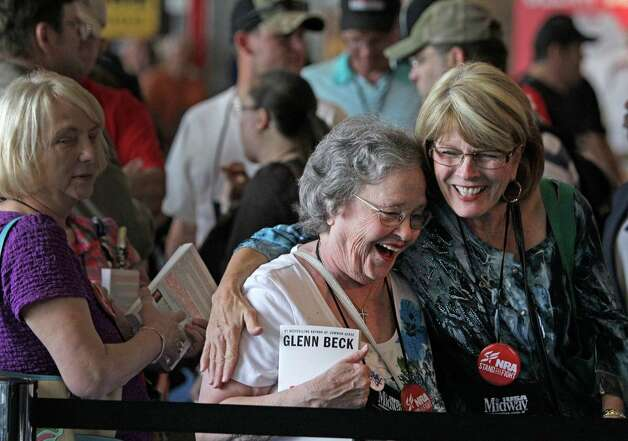 Eby Owen, center, of Dunedin, FL and Debbie Brinson, right, of San Antonio share a hug as they wait in line for the Glenn Beck book signing event during the NRA convention at the George R. Brown Convention Center  Saturday, May 4, 2013, in Houston. They woman said they became fast friends as they waiting for more than two hours. Photo: Melissa Phillip, Houston Chronicle / © 2013  Houston Chronicle