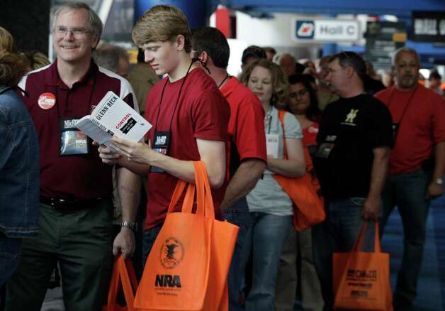 Nathaniel Foster, 15, right of College Station reads a book by Glenn Beck book as he and his dad, Tim Foster, left, wait in line for the Glenn Beck book signing event during the NRA convention at the George R. Brown Convention Center  Saturday, May 4, 2013, in Houston. Photo: Melissa Phillip, Houston Chronicle / © 2013  Houston Chronicle