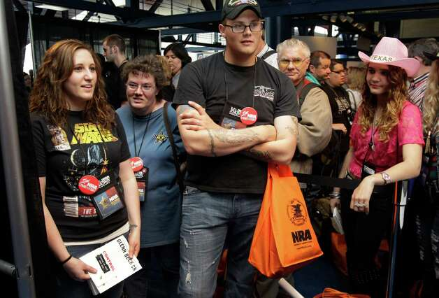 Maegan Kiser, left, of Killeen and her husband, Russell Kiser, center, wait at the beginning of the line for the Glenn Beck book signing event during the NRA convention at the George R. Brown Convention Center  Saturday, May 4, 2013, in Houston. The couple arrived four hours before the start of the event and were the first people in line. Photo: Melissa Phillip, Houston Chronicle / © 2013  Houston Chronicle