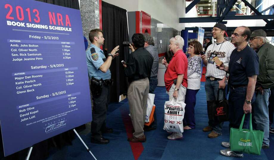 A Houston Police officer stops people from attempting to look behind curtain as they try to photograph Glenn Beck during his book signing event during the NRA convention at the George R. Brown Convention Center  Saturday, May 4, 2013, in Houston. Photo: Melissa Phillip, Houston Chronicle / © 2013  Houston Chronicle