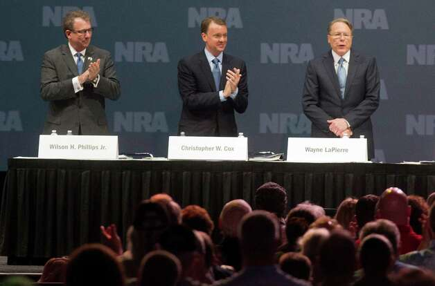 NRA executive vice president Wayne LaPierre is applauded next Chris Cox, executive director NRA-ILA and Wilson Phillips Jr., treasurer, during the NRA Annual Meeting of Members at the National Rifle Association's 142 Annual Meetings and Exhibits in the George R. Brown Convention Center Saturday, May 4, 2013, in Houston. Photo: Johnny Hanson, Houston Chronicle / © 2013  Houston Chronicle