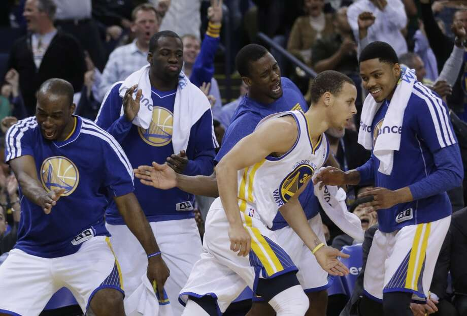 The  Warriors' Stephen Curry (30) celebrates with teammates after making a 3-pointer against the Spurs in Oakland on  April 15, 2013. Golden State won 116-106.