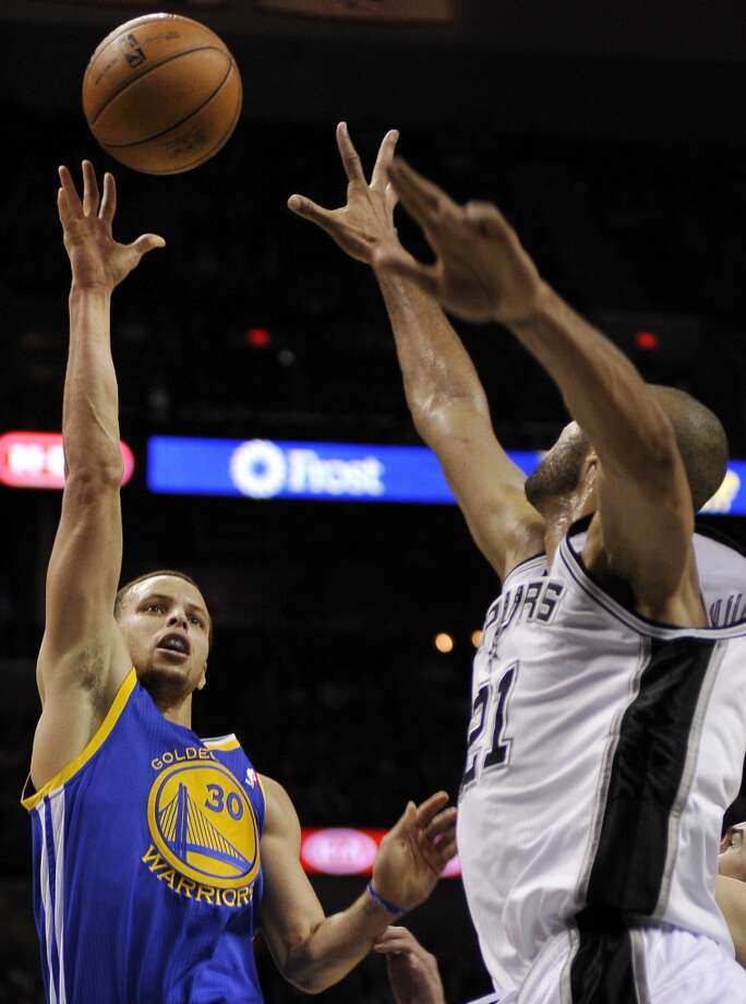 The Warriors' Stephen Curry (left) shoots over the Spurs' Tim Duncan  March 20, 2013 at the AT&T Center. The Spurs won  104-93.