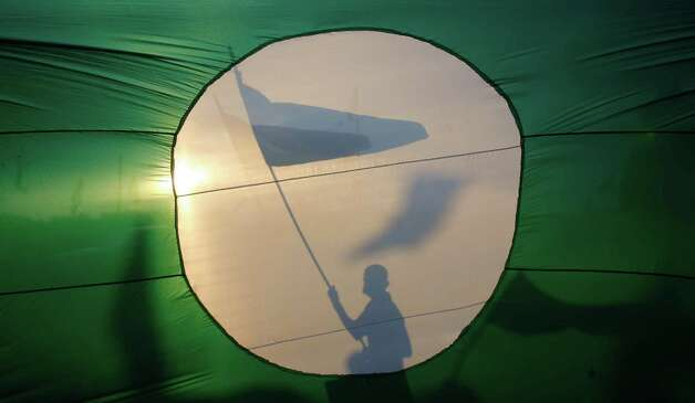 A supporter is silhouetted against a giant flag of Malaysia's opposition Pan-Malaysian Islamic Party as he waves the party's flag ahead of the upcoming general elections in Pekan, Pahang state, Malaysia, Saturday, May 4, 2013. Malaysia will hold general elections on May 5 in what could be the toughest test of the ruling coalition's 56-year grip on power in Southeast Asia's third-largest economy. (AP Photo/Lai Seng Sin) Photo: Lai Seng Sin, Associated Press / AP
