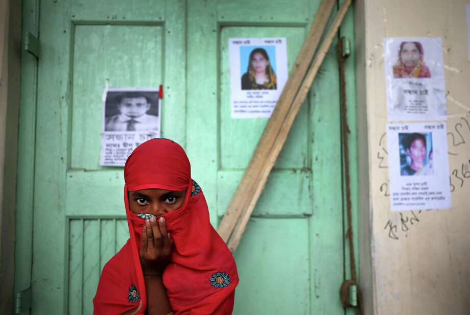 A young woman covers her nose to block out the stench from rotting bodies at a morgue where bodies recovered from the garment factory collapse are kept for identification Saturday, May 4, 2013 in Savar, near Dhaka, Bangladesh.  (AP Photo/Wong Maye-E) Photo: Wong Maye-E, Associated Press / AP