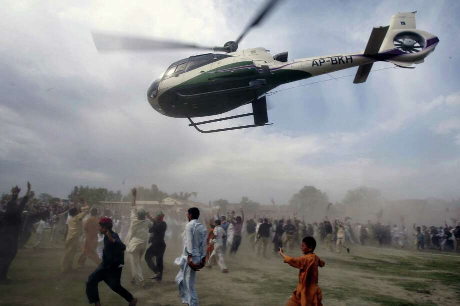 Supporters of Pakistan's former cricket star-turned-politician Imran Khan run for cover as a helicopter carrying their leader leaves after his election campaign rally in Charsadda, Pakistan on Saturday, May 04, 2013. Pakistan is scheduled to hold parliamentary elections on May 11, the first transition between democratically elected governments in a country that has experienced three military coups and constant political instability since its creation in 1947. (AP Photo/Mohammad Sajjad) Photo: Mohammad Sajjad, Associated Press / AP