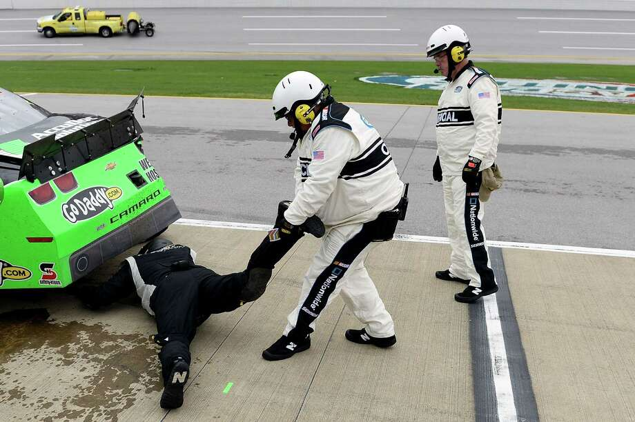 A NASCAR official pulls a crew member the #34 AccuDoc Solutions / GoDaddy Chevrolet driven by Danica Patrick (not pictured) out from under the car due to a safety concern as the crew member was inspecting damage on the car in the pits during the NASCAR Nationwide Series Aaron's 312 at Talladega Superspeedway on May 4, 2013 in Talladega, Alabama. Photo: Patrick Smith, Getty Images / 2013 Getty Images