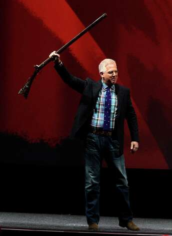 Glenn Beck takes the stage holding an antique rifle Saturday at the NRA convention. Photo: Melissa Phillip, Staff / © 2013  Houston Chronicle