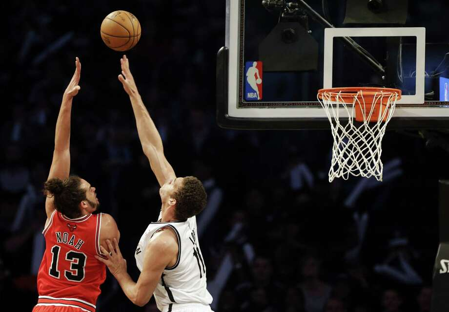 Chicago Bulls center Joakim Noah, left, shoots against Brooklyn Nets center Brook Lopez during the first half in Game 7 of their first-round NBA basketball playoff series in New York, Saturday, May 4, 2013. (AP Photo/Julio Cortez) Photo: Julio Cortez